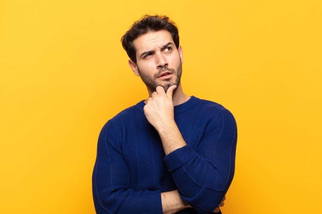 גבר עם חולצה כחולה ורקע צהוב במבט של שאלה