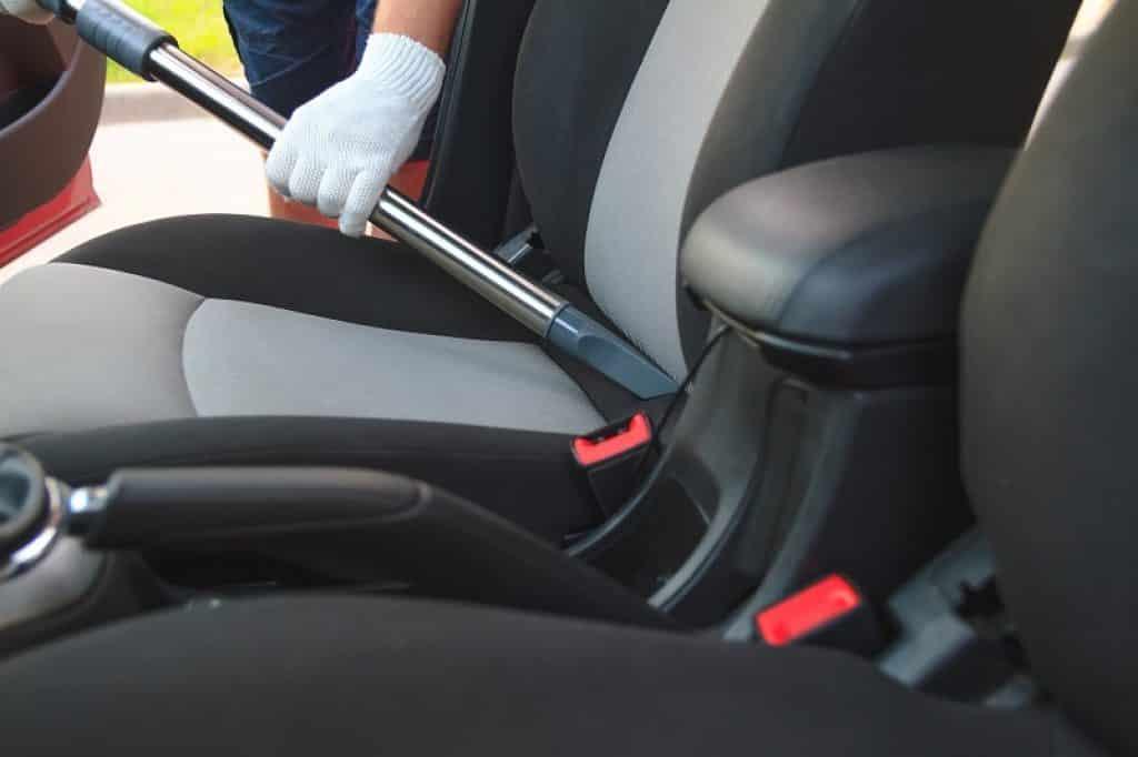 ידיים עם כפפות בזמן ניקוי של מושב קדמי ברכב