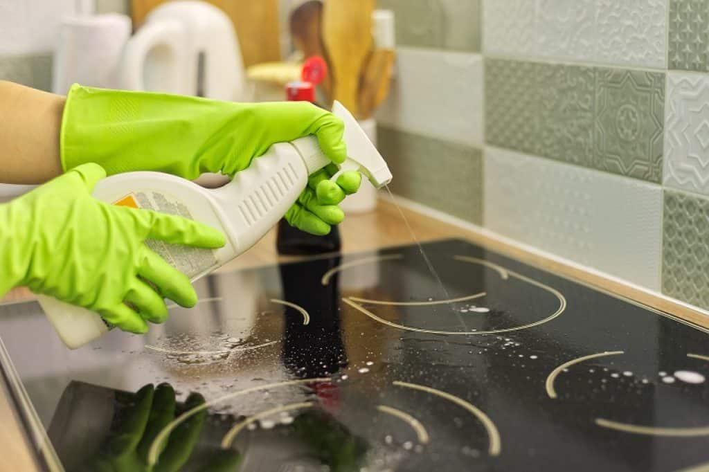 ידיים עם כפפות צהובות מנקות כיריים אינדוקציה