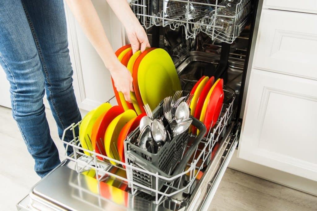 ידיים של אישה מחזיקה צלחות צבעוניות במטבח