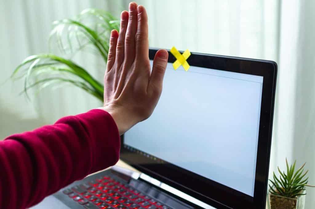 יד חוסמת מצלמת אינטרנט יחד עם דבק צהוב על מסך המחשב