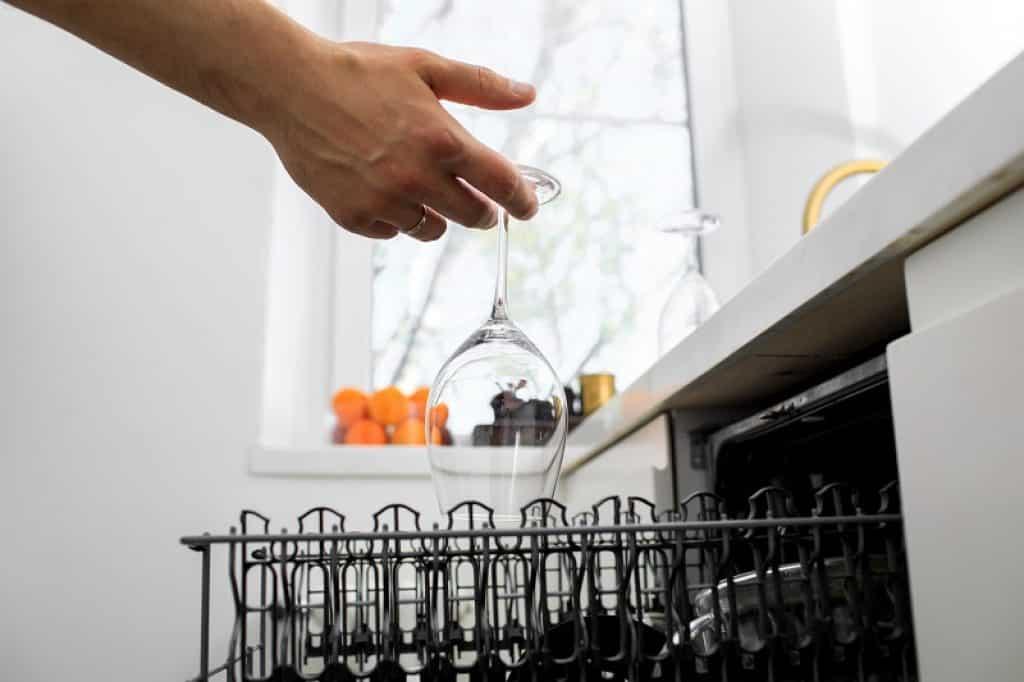 יד של בחור מניח כוס יין הפוכה בתוך מדיח כלים צר