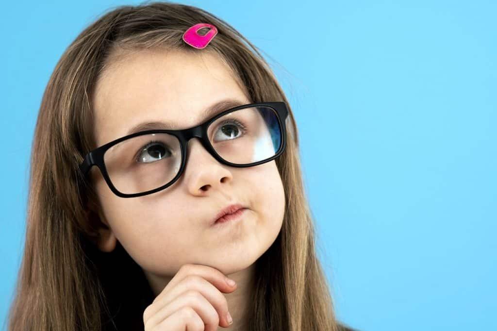 ילדה עם משקפיים על רקע תכלת שואלת שאלה