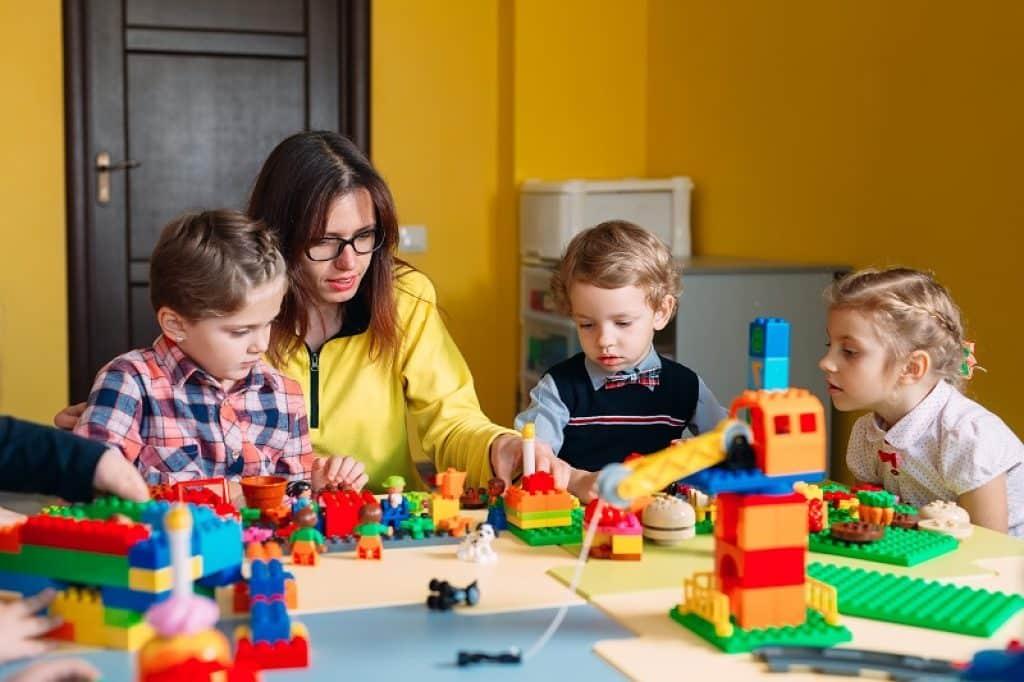 ילדים משחקים יחד עם הורה בישיבה על הרצפה