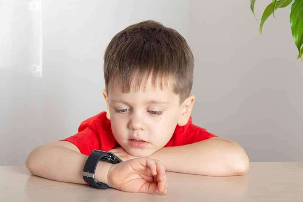ילד קטן מסתכל על שעון חכם לילדים