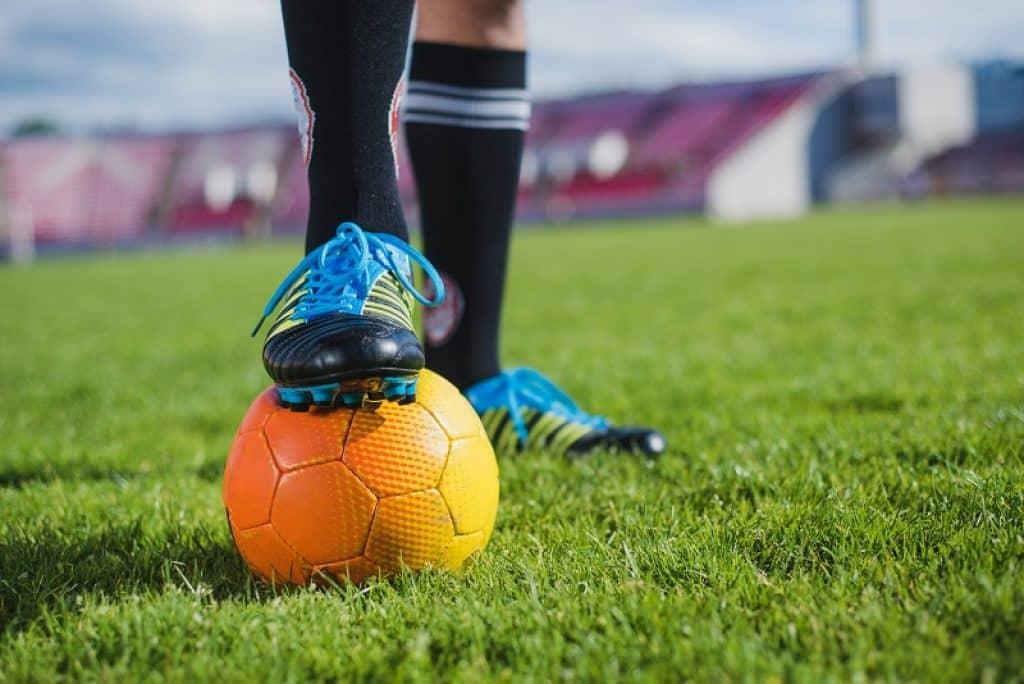 כדור כתום ונעלי כדורגל בגווני כחול ותכלת