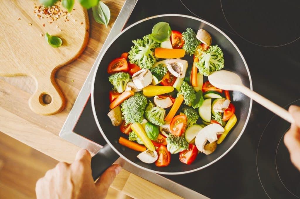 כף עץ מערבבת תבשיל ירקות צבעוני במחבת שחורה