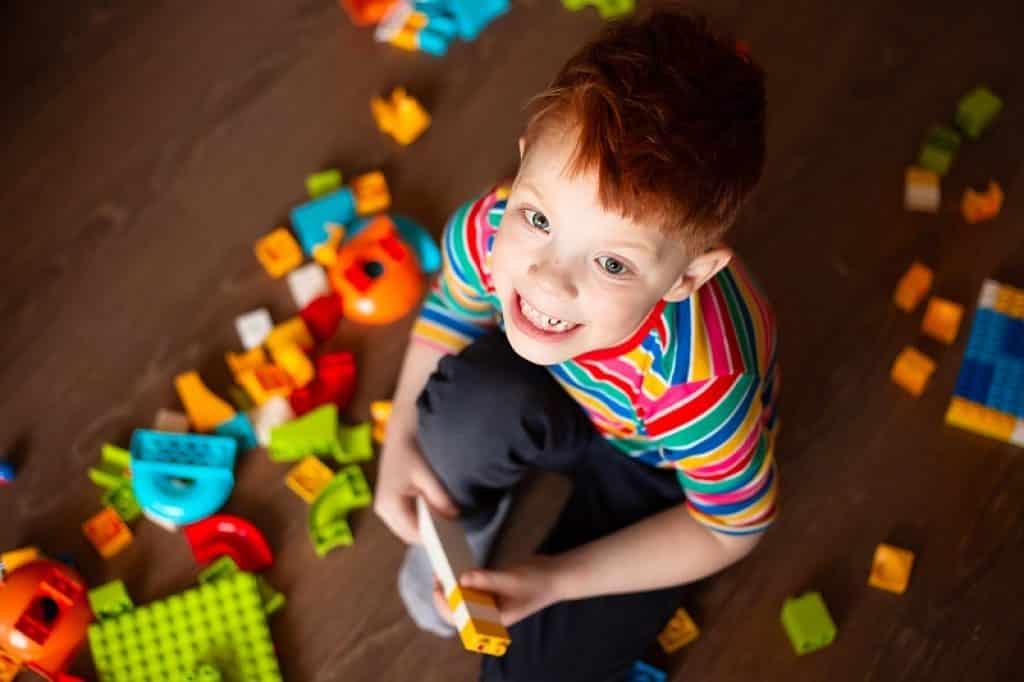 מבט על ילד מסתכל למעלה משחק בצעצועים על הרצפה