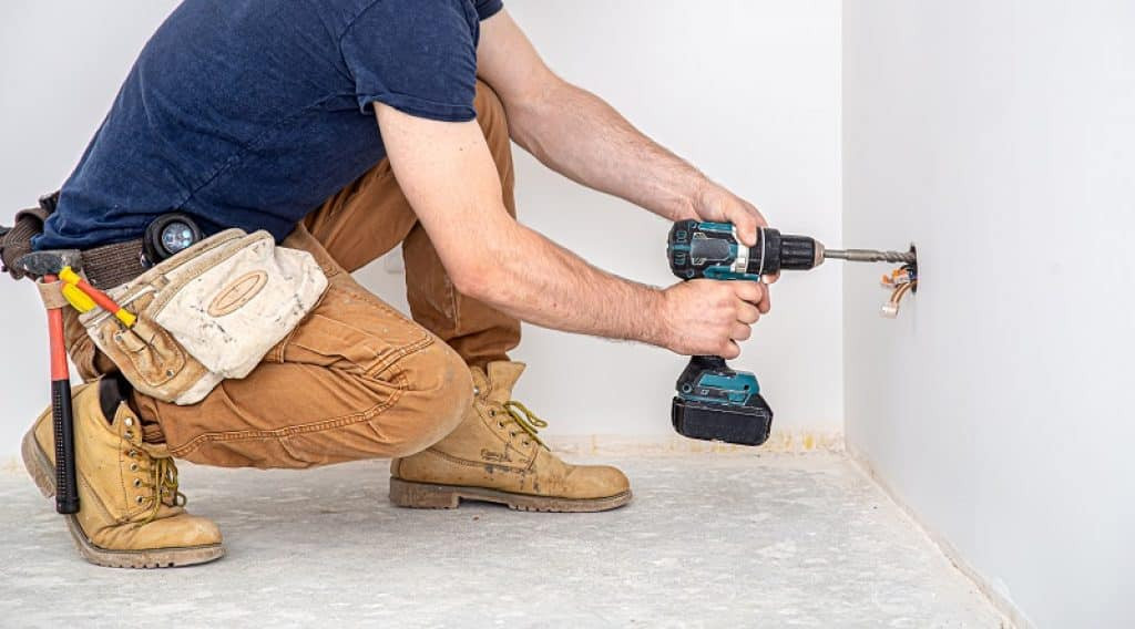 מקצוען קודח חור בקיר בבגדי עבודה קורע ברך