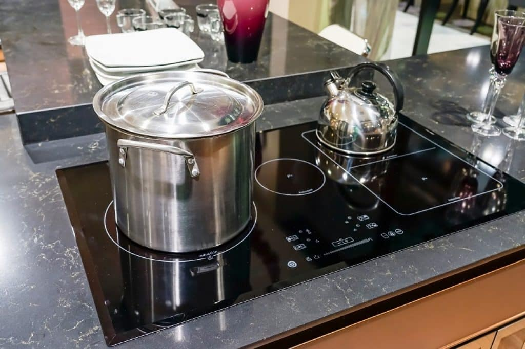 משטח בישול גדול שחור עם סיר נירוסטה וקומקום