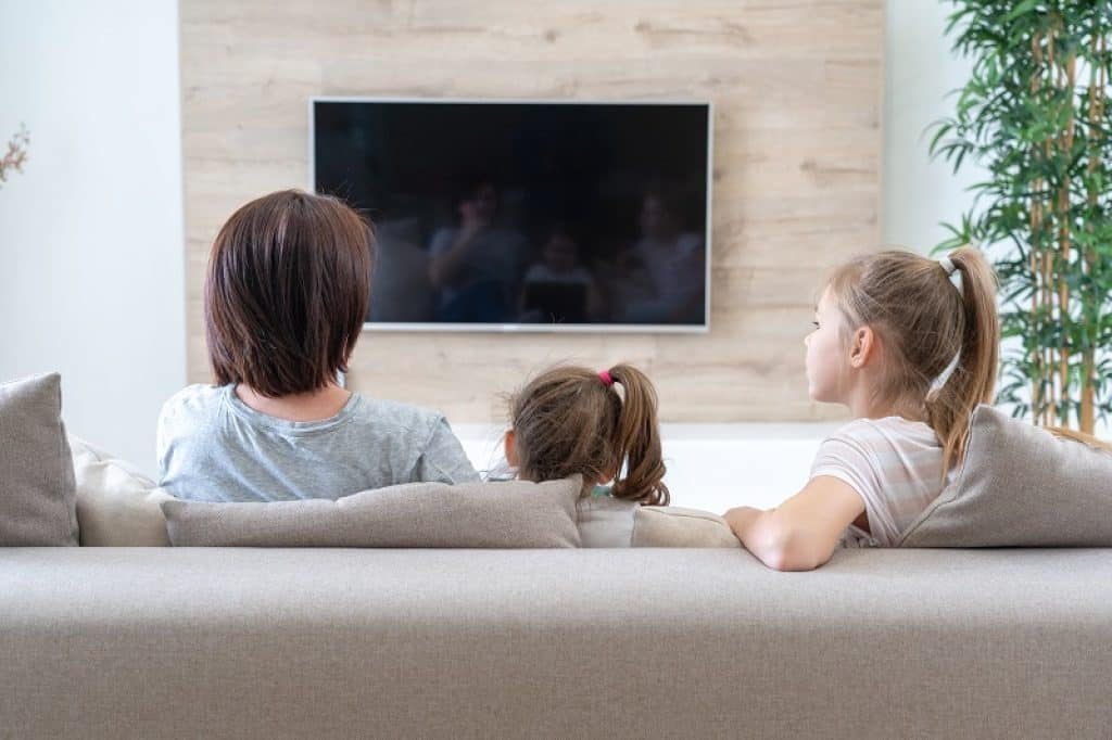 משפחה צופה בטלוויזיה 65 אינץ' בסלון