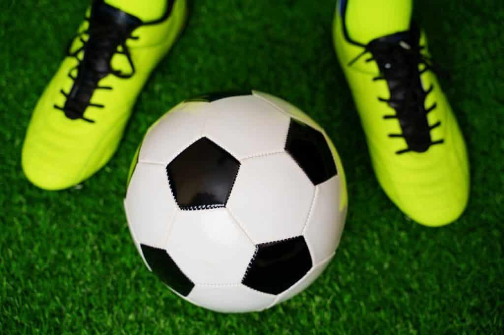 נעלי כדורגל צהוב שחור על כר דשא סינתטי