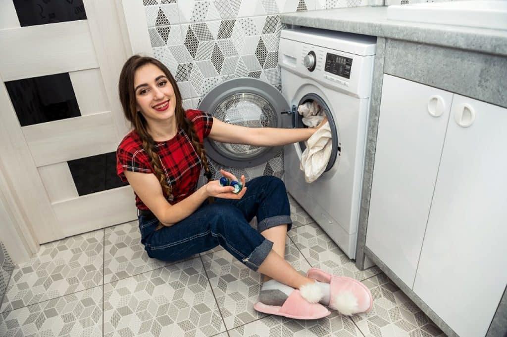 נערה מאופרת עם נעלי בית ורודות מחייכת ועושה כביסה