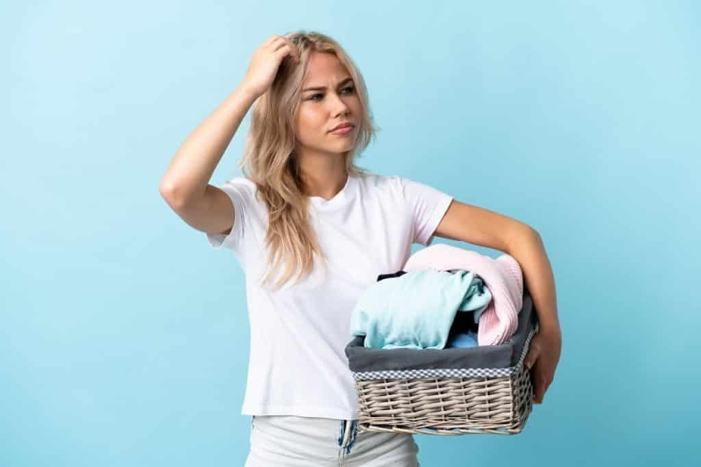 נערה עם שיער בלונדיני מחזיקה בגדים נקיים במבט של שאלה