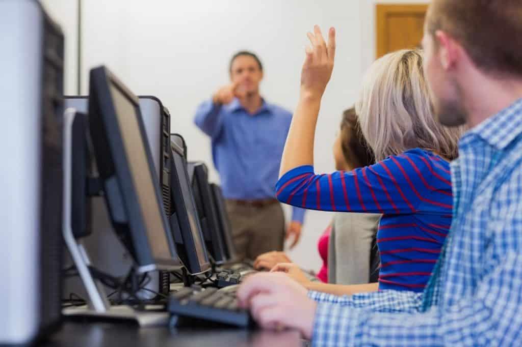 סטודנטית מרימה את היד כדי לשאול את המרצה שאלה