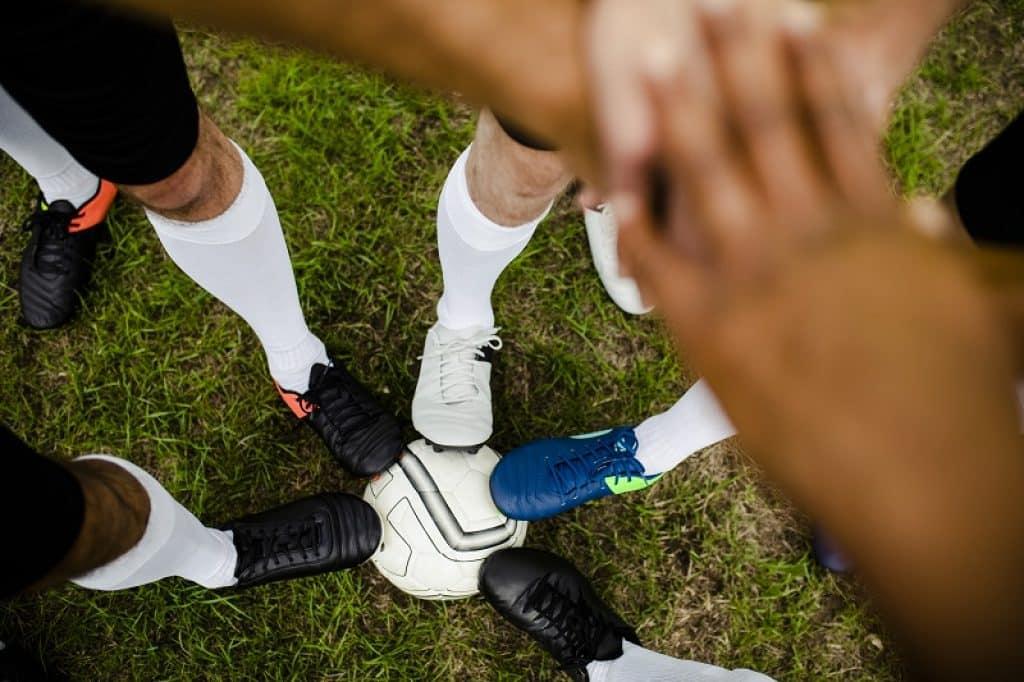 קבוצה של שחקנים מניחים את הרגל על כדור ומשלבים ידיים