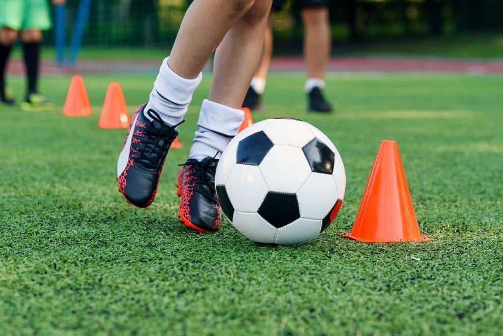 רגליים של נער עם גרביים לבנות רץ עם כבור בין קונוסים בדשא