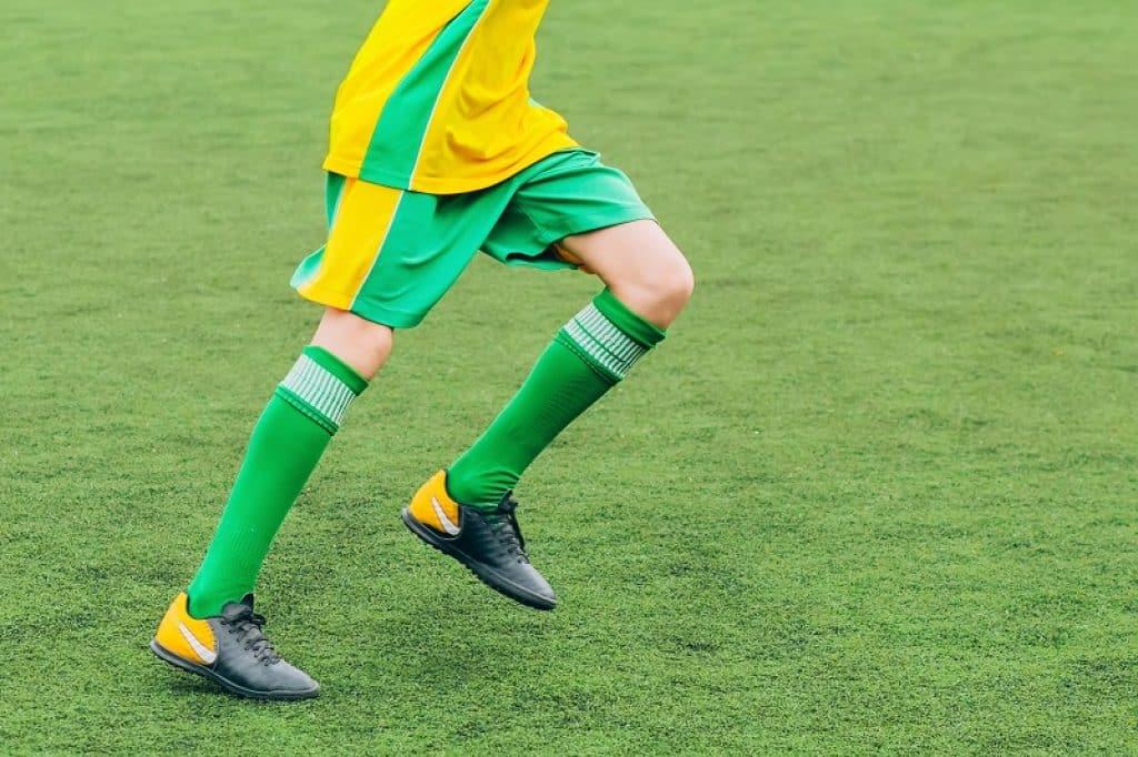 רץ על הדשא בזמן משחק עם מדים של נבחרת ברזיל