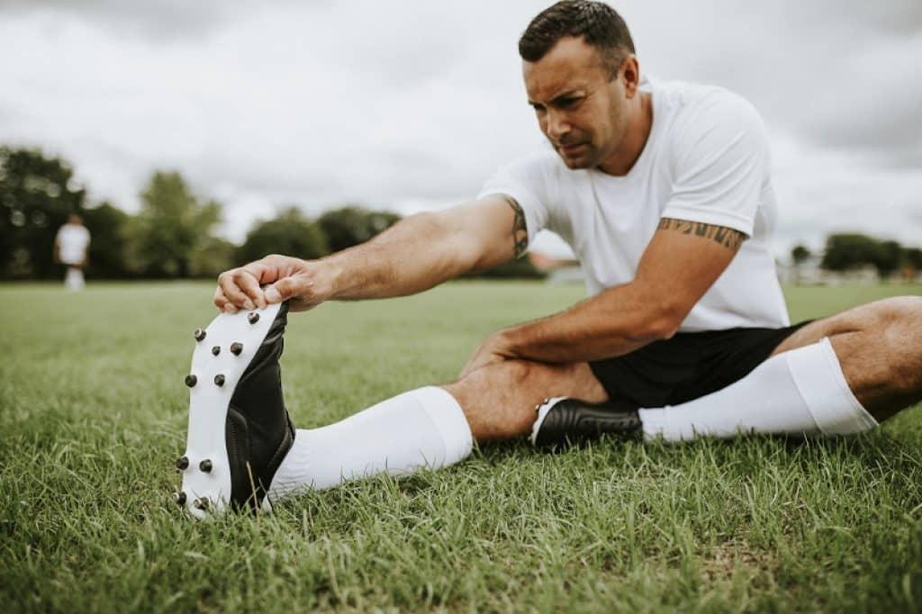 שחקן עושה מתיחות בדשא לקראת המשחק