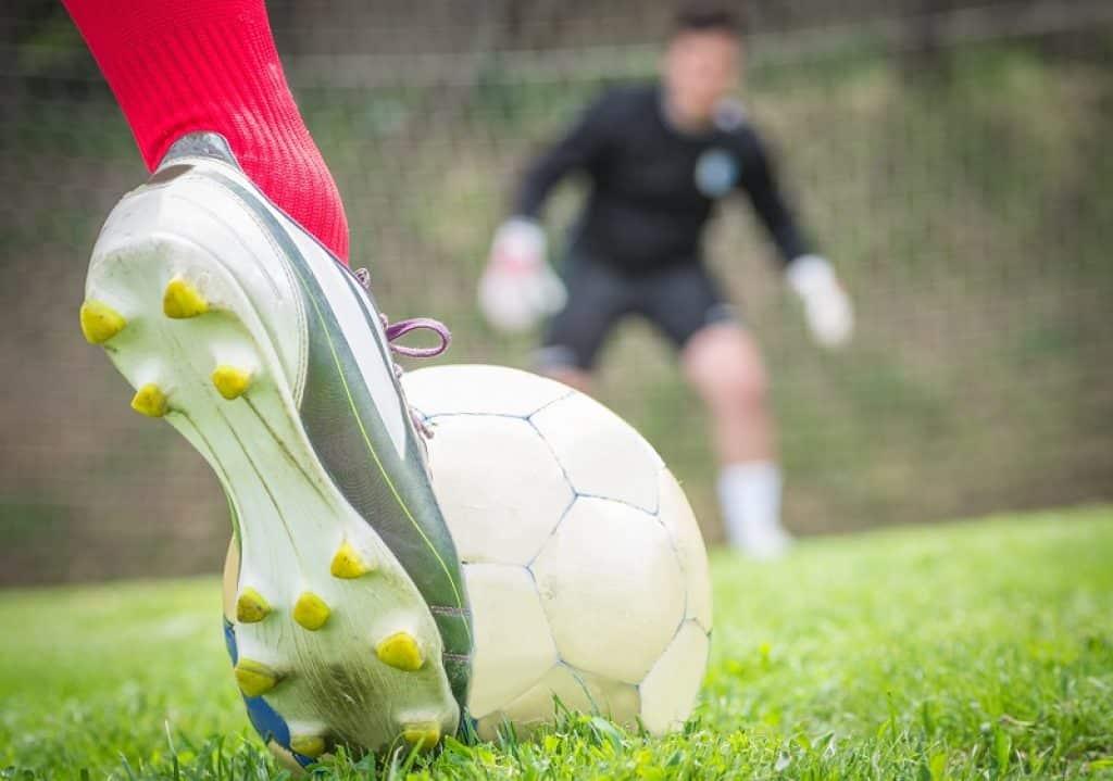 שחקן עם גרביים אדומות בועט כדור לכיוון השער