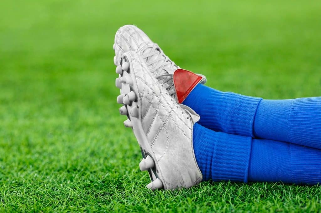 שחקן עם גרביים כחולות ונעלי כדורגל אפורות בזמן מנוחה