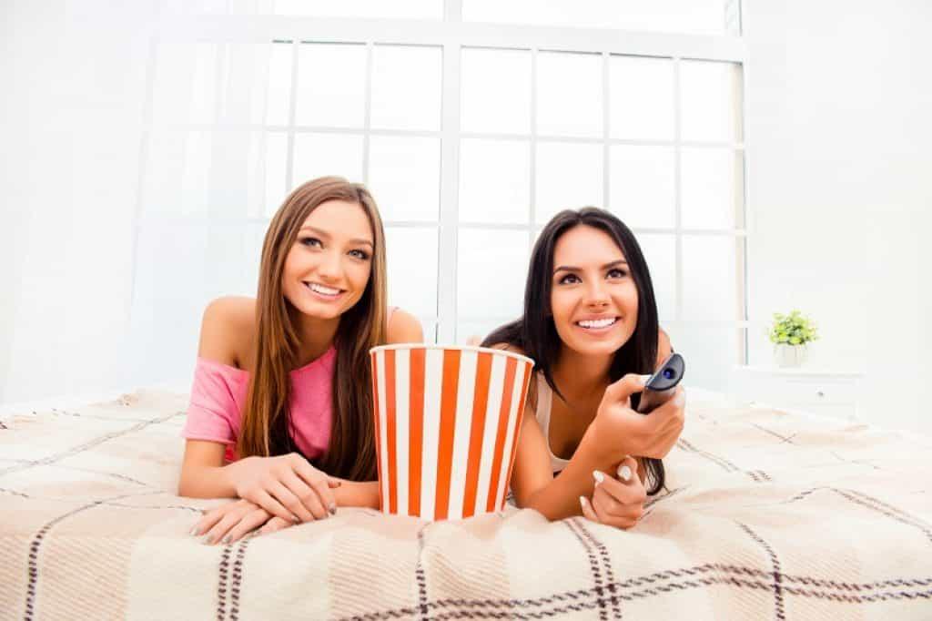 שתי בחורות שוכבות במיטה עם דלי פופקורן צופות בסרט ומחייכות