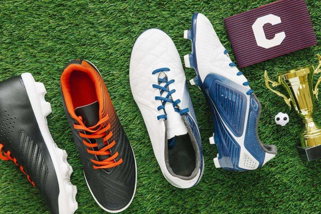 שתי זוגות נעלי כדורגל מונחים על הדשא עם גביע