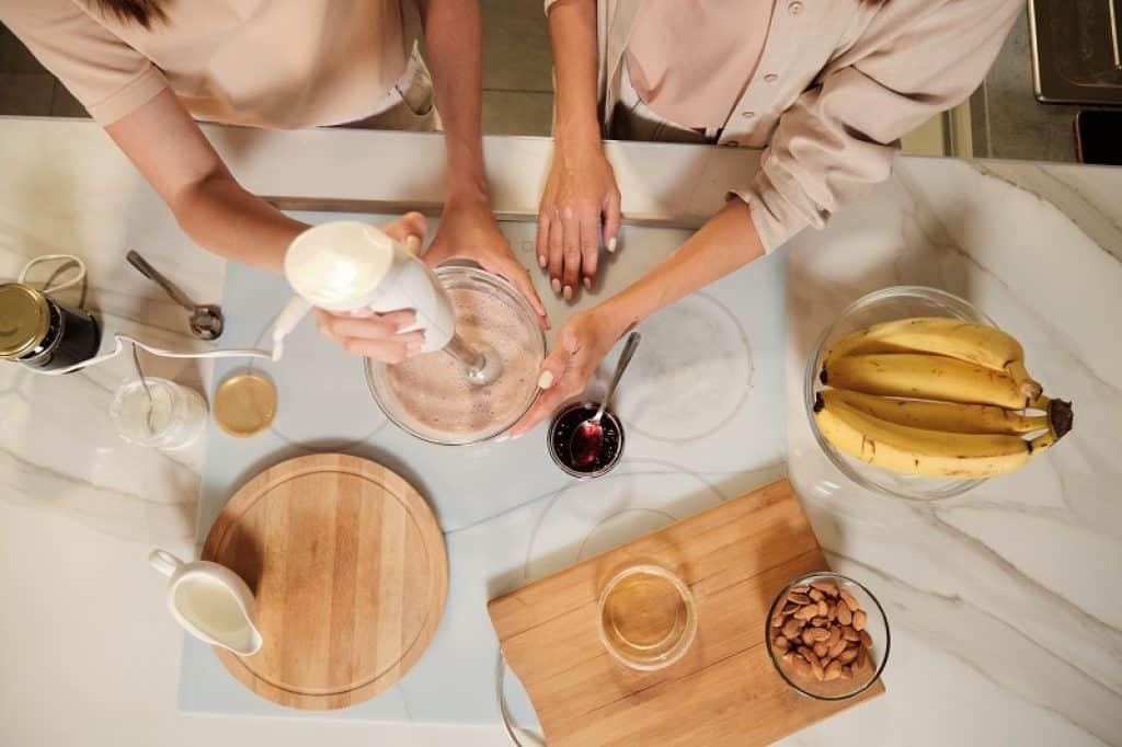 שתי נשים מערבלות מצרכים כדי להכניס למכונת גלידה