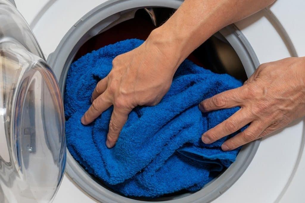 תמונה של ידיים של גבר מכניסות שמיכה כחולה למכונת כביסה AEG