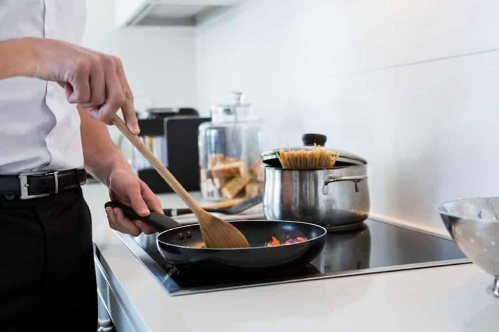 תקריב של בחור עם חגורה מבשל במחבת עם כף עץ
