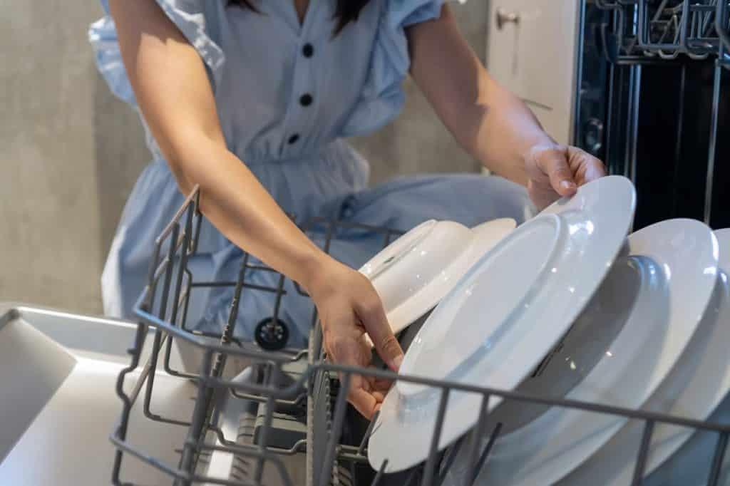 תקריב של ידיים מחזיקות צלחת במגירת הכלים