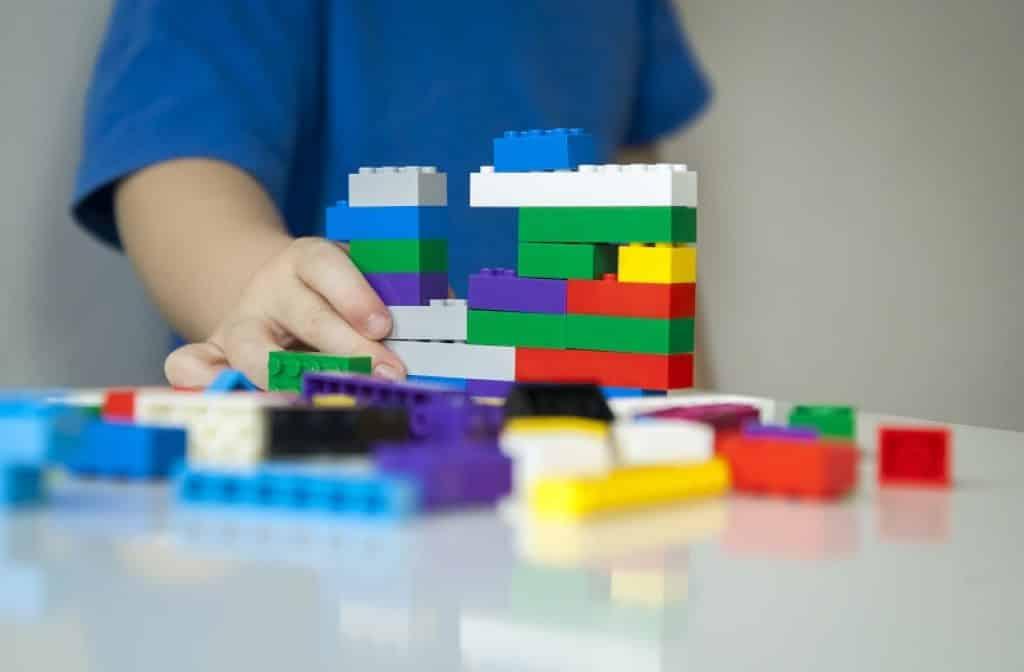 תקריב של ילד עם חולצה כחולה משחק בצעצועי פלסטיק