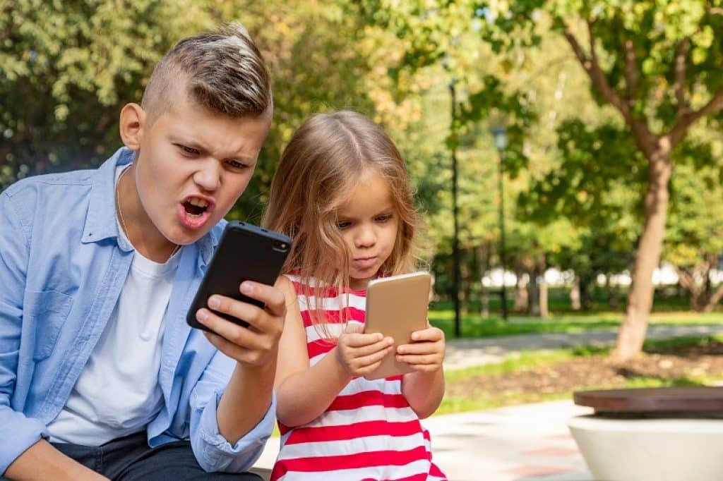 אח ואחות יושבים ביחד בגינה ומשחקים בטלפונים שלהם