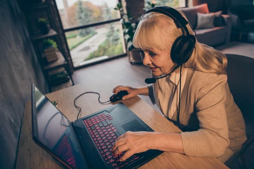 אישה מבוגרת בלונדינית עם אוזניות מול מסך