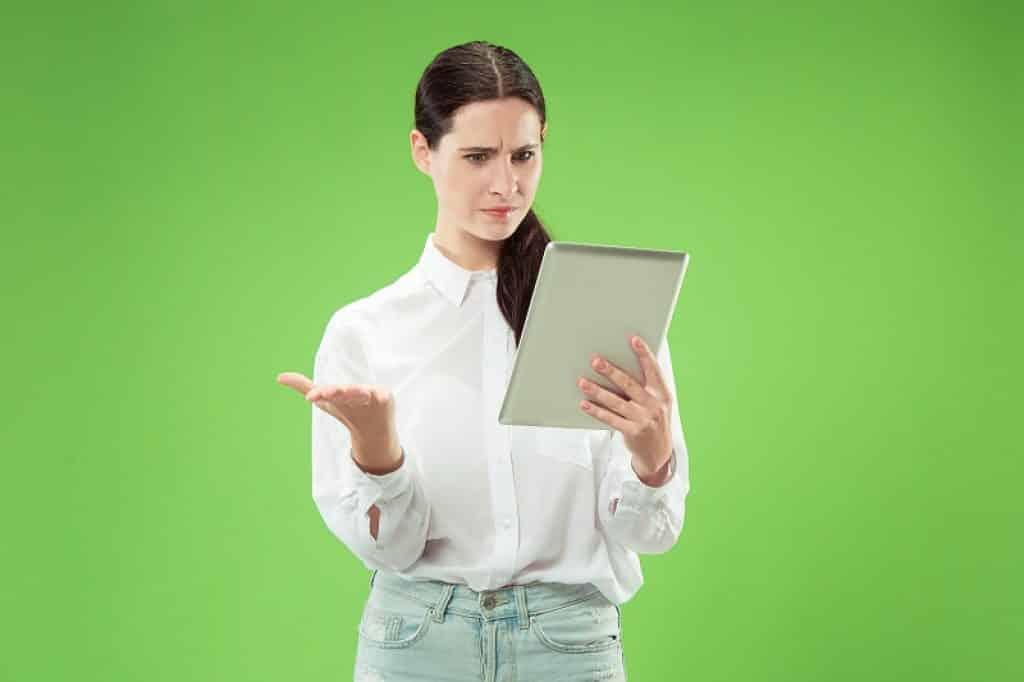 אישה צעירה מסתכלת על המסך בהבעת שאלה