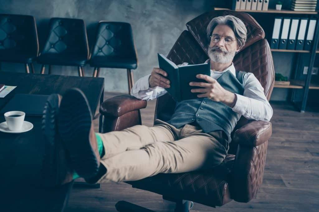 איש מבוגר יושב במשרד חשוך וקורא ספר