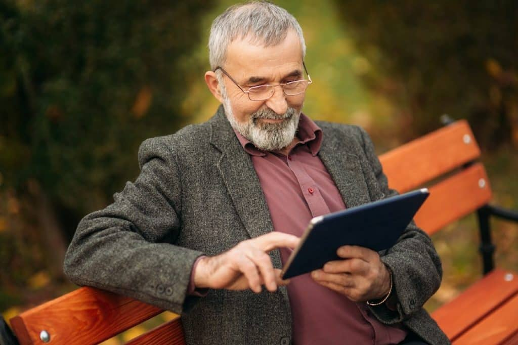 איש מבוגר יושב על ספסל בגינה מסתכל על טאבלט ומחייך