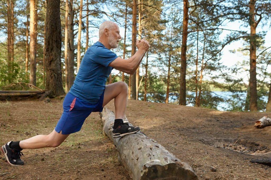 איש עם שיער וזקן לבנים עושה מתיחות על גזע עץ