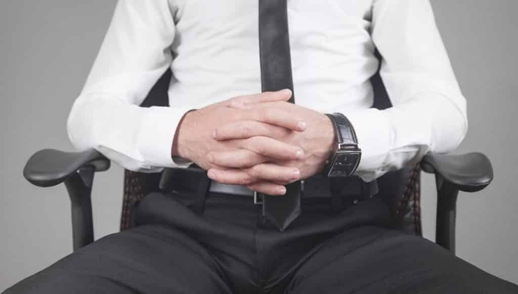 איש עסקים עם חליפה יושב על כיסא משרדי