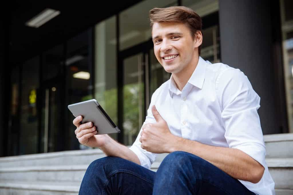 איש צעיר יושב על המדרגות ליד מקום העבודה שלו