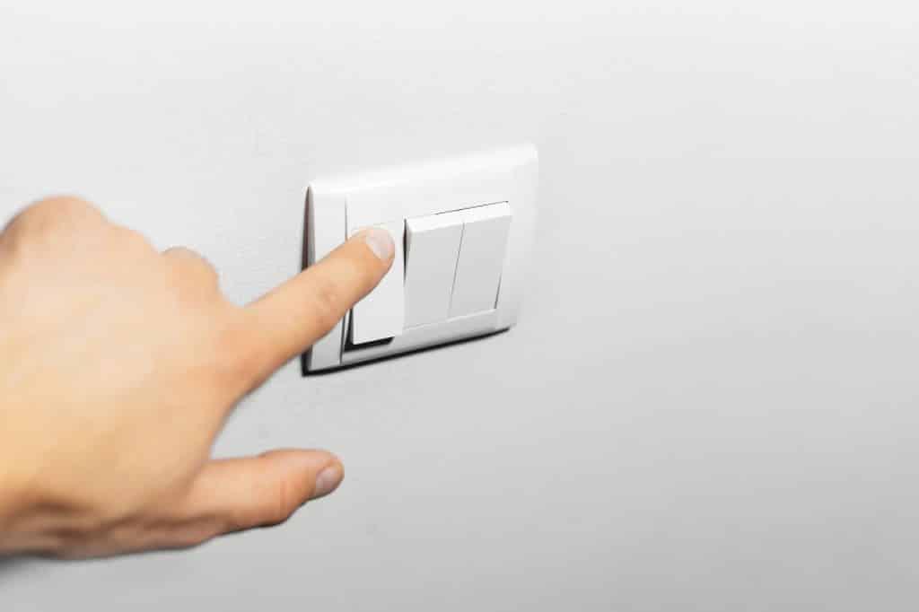 אצבע מדליקה מפסק חשמל על הקיר