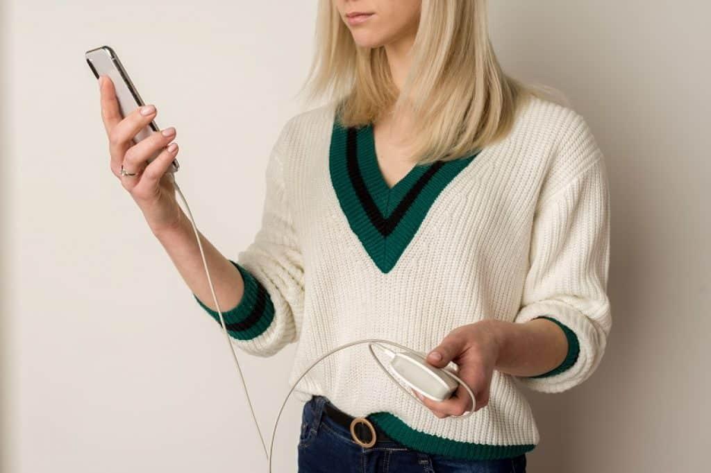 בחורה בלונדינית עם סוודר לבן מחזיקה טלפון
