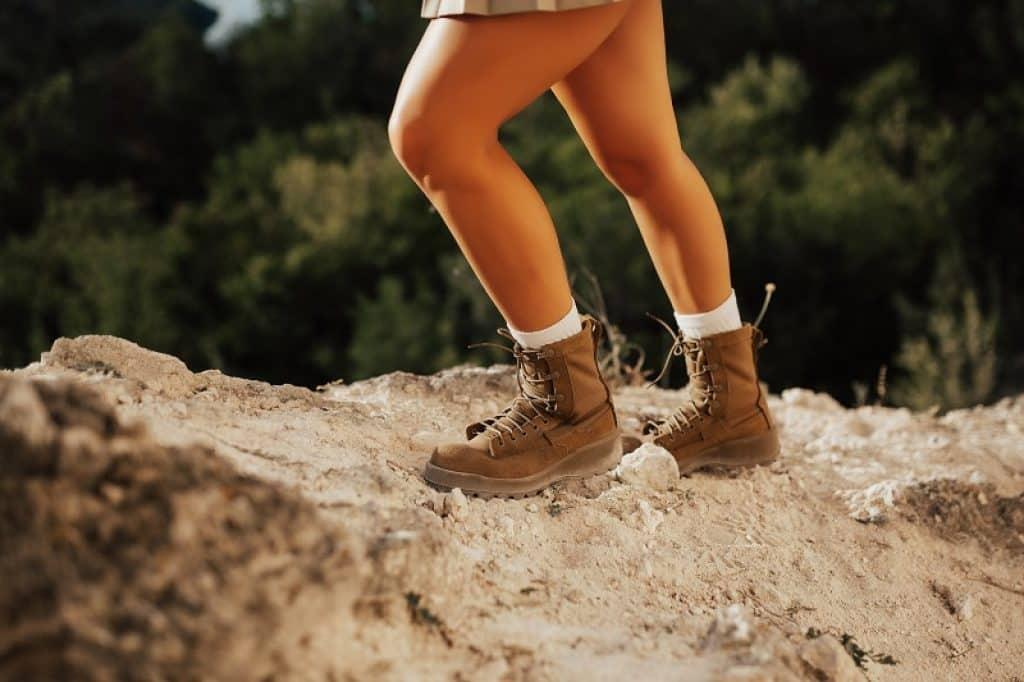 בחורה עומדת  עם נעלי הליכה ועבודה על סלע