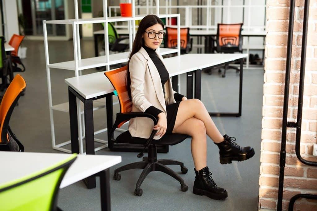 בחורה עם משקפיים יושבת על כיסא משרדי עם ריפוד רשת