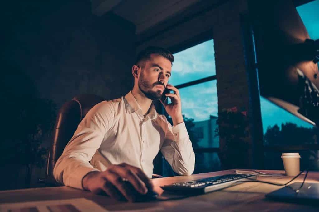 בחור מבוגר מדבר בטלפון תוך כדי שהוא מסתכל במסך המחשב