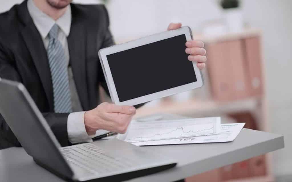 בחור עם חליפה ועניבה יושב ליד שולחן עם מחשב