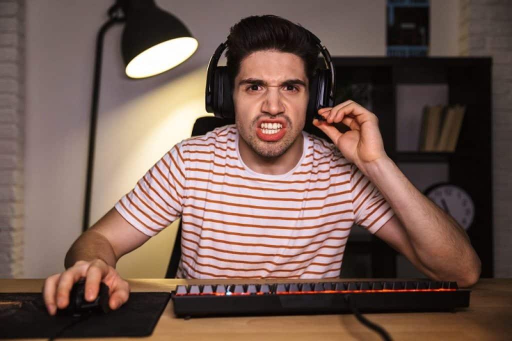 בחור צעיר עם אוזניות מרותק למשחק מחשב