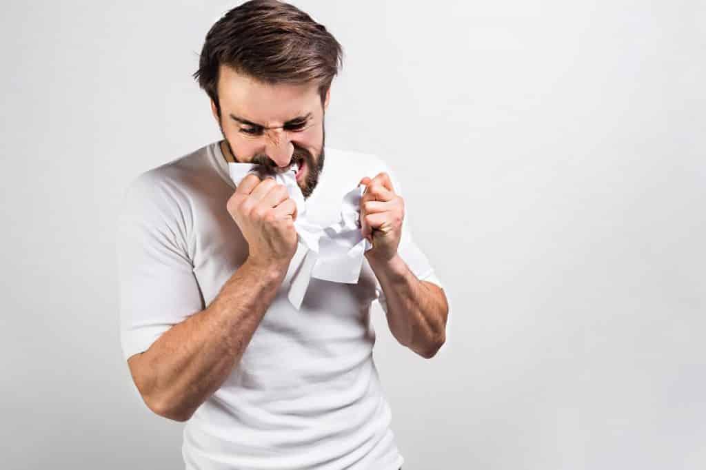 בחור צעיר קורע דף עם השיניים כי אין לו מגרסת נייר