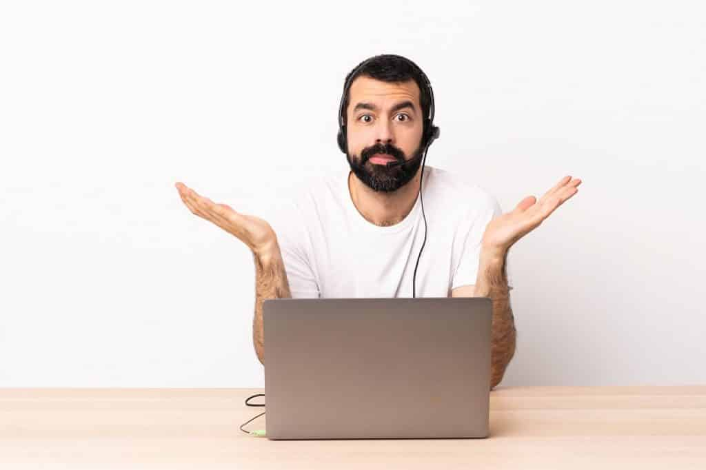 גבר עם זקן בחולצה לבנה ואוזניות מול מחשב נייד שואל שאלה