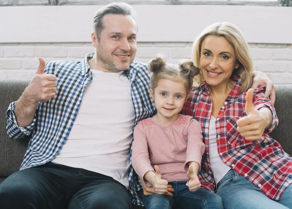 זוג הורים וילדה יושבים על הספה עם פרצופים מרוצים